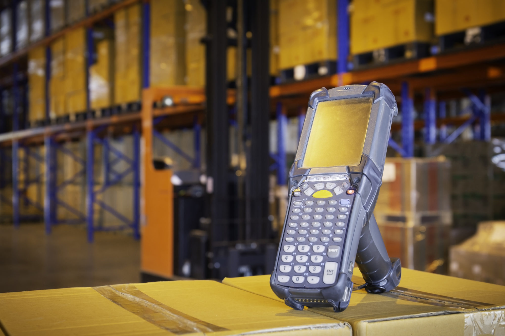 Bluetooth barcode scanner on cardboard box in storage warehouse, warehouse inventory management the products.