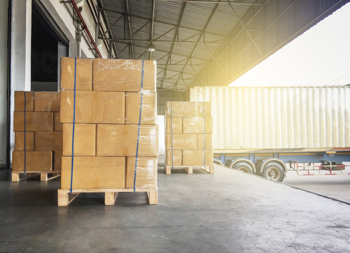 Warehouse Cargo Courier Shipment. Stack Of Cardboard Boxes On Wooden Pallet And Truck Docking At Warehouse